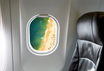 Beautiful beach through aircraft window onto jet engine
