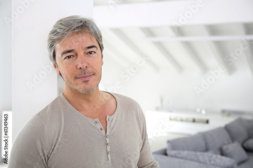 Mature handsome man standing in modern house