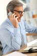 Senior businessman in office using smartphone