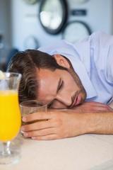 Drunk businessman asleep on bar beside cocktail