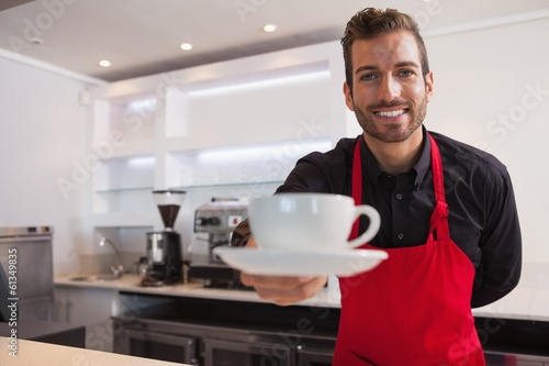 Happy barista offering cup of coffee to camera