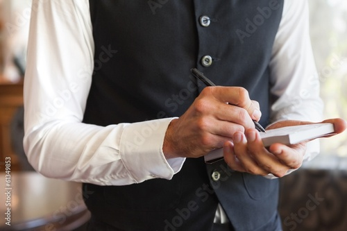 Waiter taking an order wearing a waistcoat