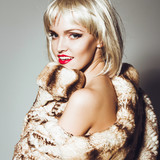 Portrait of a beautiful blonde girl in a fur coat