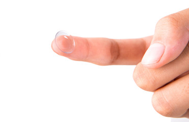 A female finger holding a contact lens