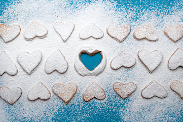Snowy cookie-hearts in lines with an empty heart in the middle