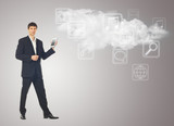 Businessman with tablet and the cloud with applications icons on