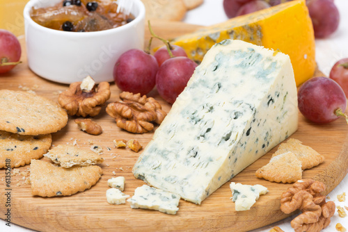 cheeses with mold, grapes, crackers, jam and nuts on a board