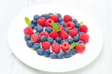 Fresh raspberries and blueberries on a plate