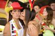 German couple of soccer sport fans kissing celebrating.
