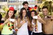 Group of happy German soccer fans holding smartphones
