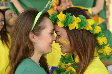 Brazilian girlfriends soccer fans kissing each other.