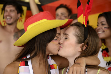 German soccer fans kissing each other celebrating.