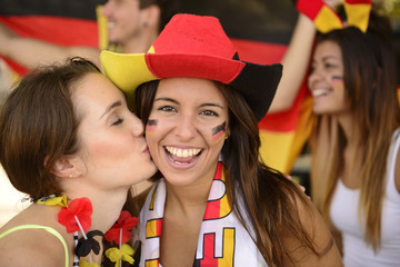 German couple of soccer sport fans kissing celebrating.