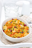 pilaf with vegetables, chicken and pomegranate in a bowl