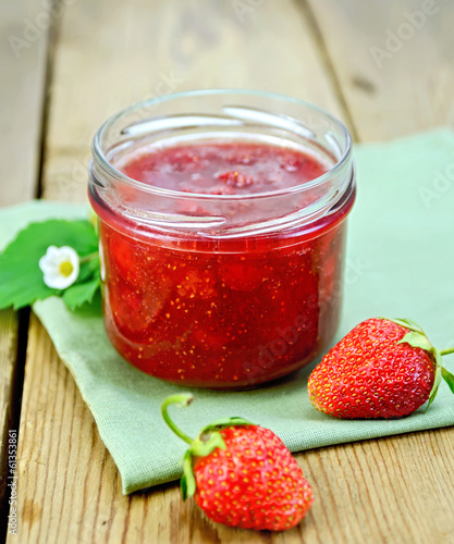 Jam of strawberry with berries on a board