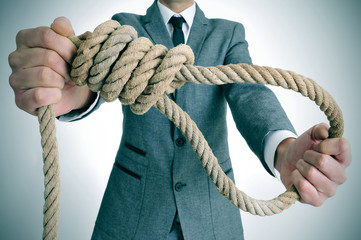 man in suit holding a rope with a hangmans noose