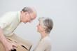 älteres paar trägt umzugskarton gemeinsam