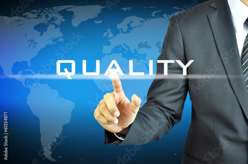 Businessman touching  QUALITY sign on virtual screen