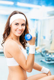 Woman exercising with dumbbell, at fitness center