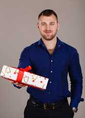 Man with muscular torso with gift box on grey background