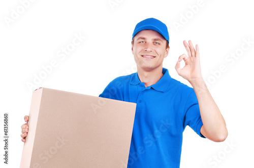Courier in blue uniform with a big box showing ok gesture