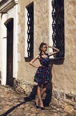 Девушка в цветном платье стоящая возле стены на улице