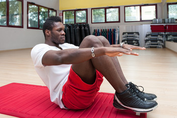 Young black man portrait exercising abdominal muscles at the gym