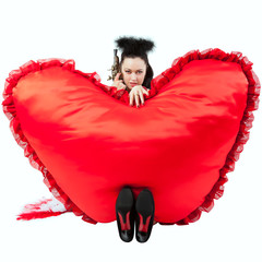A girl with a heart in the form of pillows. Valentine's Day.