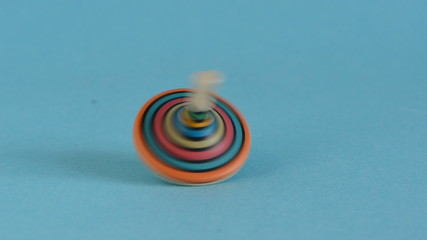 colorful wooden whirligig toy in motion on blue background