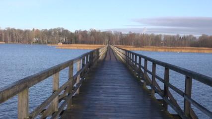 long empty wooden bridge on autumn lake