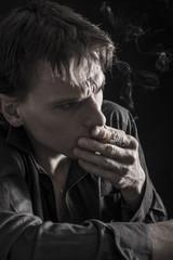 Close up of depressed man smoking cigarette