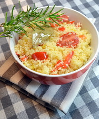Couscous with vegetables cooked in a red bowl