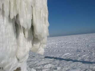 Обледеневший пирс на пляже на фоне замерзшего моря