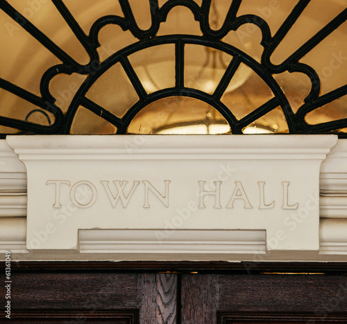 Town Hall sign carved in stone above a wooden door.