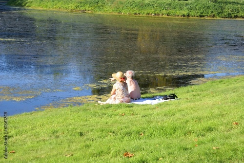 elderly couple sitting relaxing at lakeside