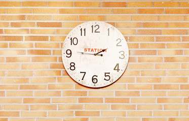 An old station clock over bricks wall