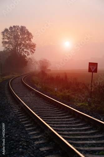 Railroad track during autumn foggy morning