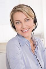 Kundenberatung: ältere blonde Frau mit Headset im Büro