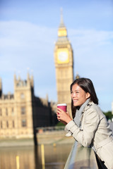 London woman happy by Big Ben drinking coffee