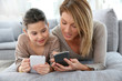 Mother and daughter playing games with smartphone