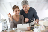 Couple in home kitchen cooking together and using tablet