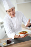 Chef in kitchen presenting italian dish