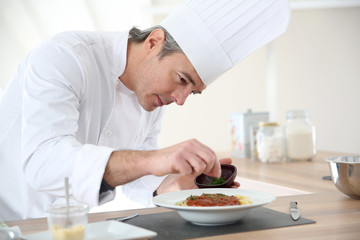 Chef in kitchen preparing italian dish