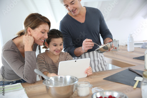 Family in home kitchen preparing pastry