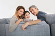 Happy family of three relaxing in sofa
