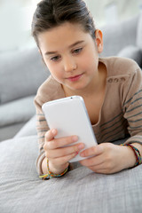 Little girl playing with smartphone at home