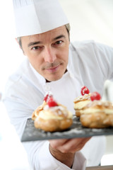 Chef holding plate of pastries towards camera