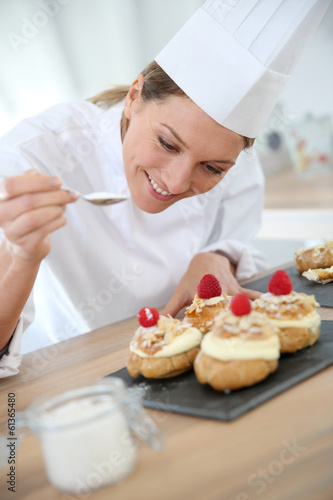 Professional cook spreading powdered sugar on cream puffs - 61365480