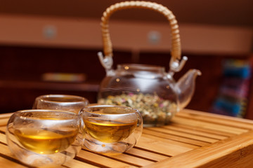Herbal tea in a glass teapot on a wooden board