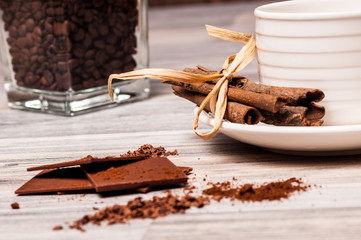 Cinnamon sticks, chocolate and a cup of coffee